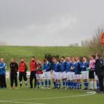 De spelers van De Valken op de middencirkel. Vanwege twee sterfgevallen binnen de club werd een indrukwekkende minuut stilte gehouden.
